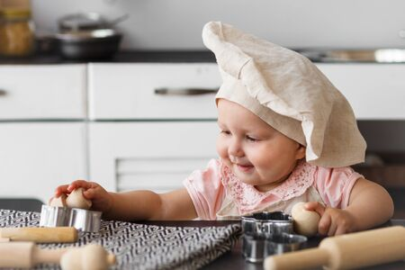 Cute baby cook with wooden tools in a cap and an apron making cookies