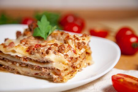 Portion of tasty italian lasagne served on white plate. Stock Photo