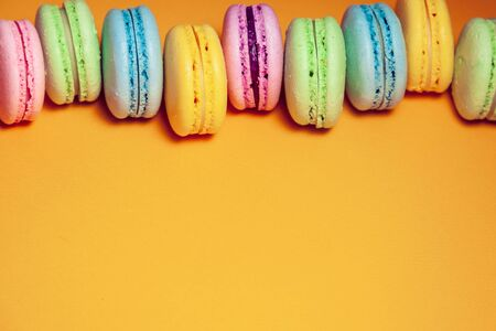Different colorful macaroons on orange background