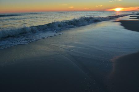 onto: waves crashing onto beach at sunset