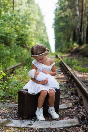 looking at baby: Girl sitting on a suitcase at the railway and holding a baby doll and looking at her with love Stock Photo
