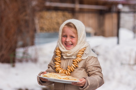 Sweet girl in old Russian scarf on the head with lengths in a plate and bread-rings around the neck walking down the street