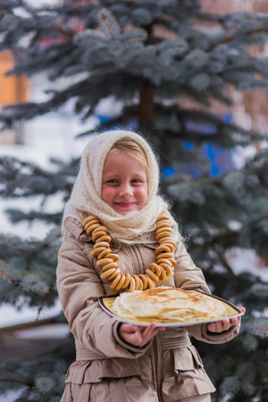 sudarium: Sweet girl in old Russian scarf on the head with lengths in a plate and bread-rings around the neck walking down the street