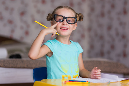 note booklet: Joyful girl schoolgirl with pencil in hand and glasses Stock Photo