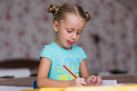 note booklet: Girl learns lessons carefully. She writes in a notebook with a pencil. Stock Photo