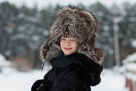 Girl in a fur hat winter day