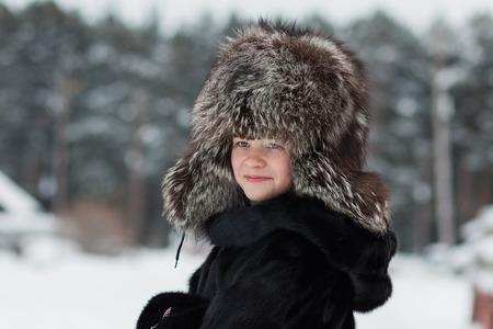 yule log: Girl in a fur hat winter day