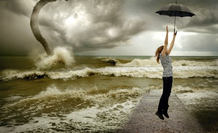 flying up girl with umbrella over sea tornado  background