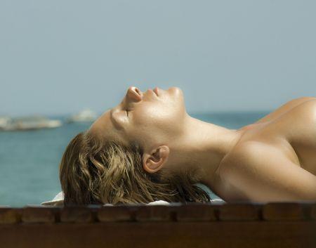sunburned: beauty girl tanning on the beach background photo