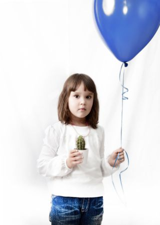 little girl with ball and cactus in hands over white background photo