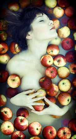 The beautiful girl floating in apples photo