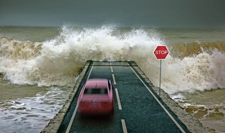 the flood tide: car rushing along the highway towards the giant wave