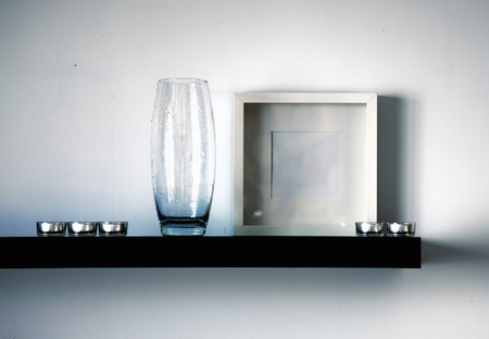 black shelf with vase,frame and candles photo