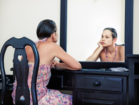 woman mirror: the woman looks in the mirror in vintage interior Stock Photo