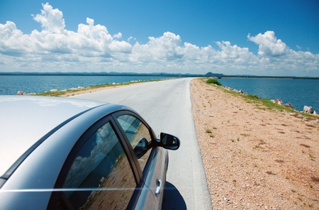 Car driving across ocean by the road Stock Photo
