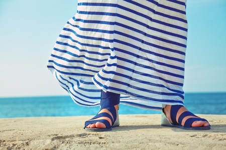 female feet in billowing dress against the background of the ocean photo
