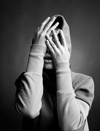 young woman hide her face in her hands photo