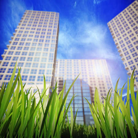 aspiring: green grass and skyscrapers, aspiring to the sky in the backgroun  Shallow DOF Stock Photo