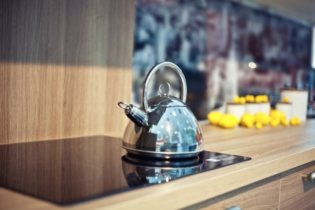 Shiny tea kettle on the kitchen table  beautiful diepth of field effect  photo
