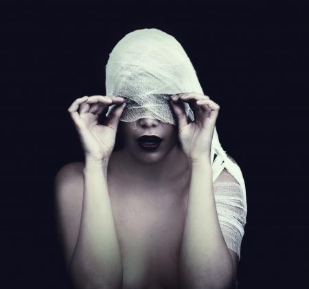 mujer en vendaje sobre fondo negro concepto de estilo gótico