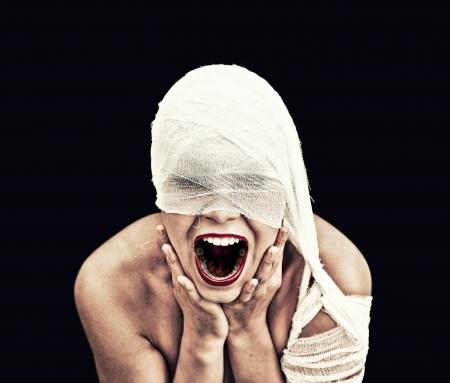 b�se augen: schreiende Frau im Verband auf schwarzem Hintergrund gotischen Stil Konzept