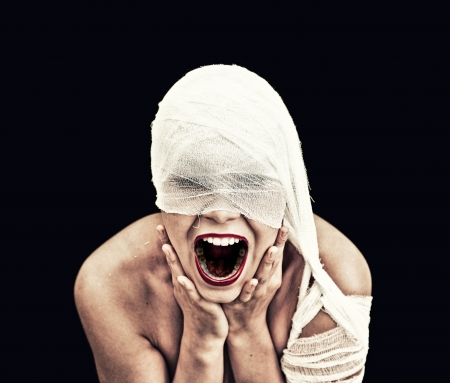 evil eye: screaming woman  in bandage over black background  gothic style concept