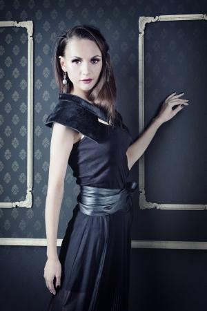 styled interior: beautiful woman in elegant dress posing in  vintage  interior Stock Photo