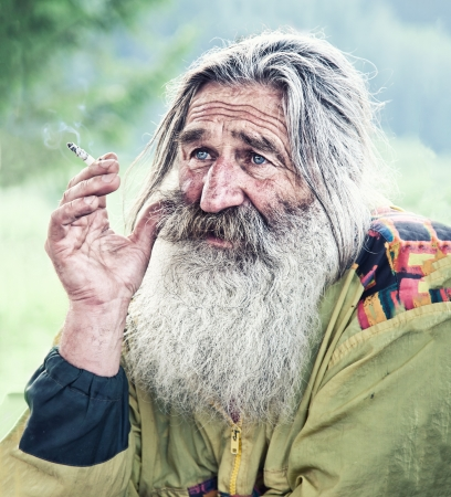 hombre viejo: retrato de fumar anciano con barba gris Foto de archivo