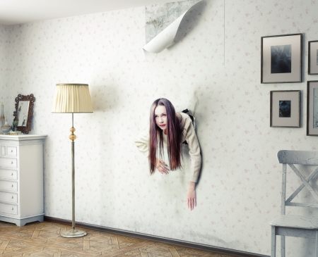 woman climbs through the wall into the room photo