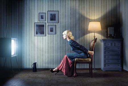 Jonge vrouw zittend op een stoel in vintage interieur en het kijken naar retro tv Ze is erg verbaasd tijdens het kijken naar tv in een donkere kamer Stockfoto