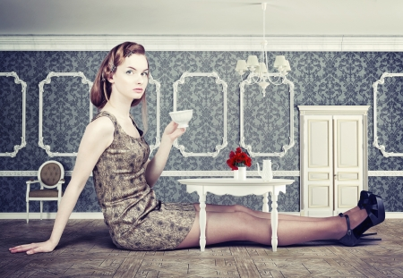 beautiful woman in little room drink a cup of tea (concept) photo