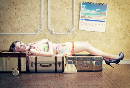 young woman, sleep on the luggage, waiting her vacation photo