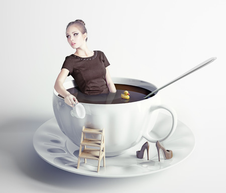 creative concept: little beautiful woman takes a bath in cup of coffee (creative concept) Stock Photo