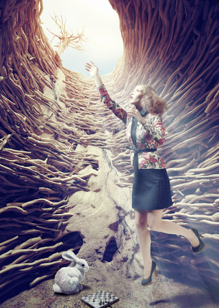 animal den: girl flies out of a deep hole toward the sunlight. creative concept Stock Photo