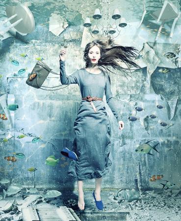 sumergido: una mujer bonita bajo el agua en el interior inundado. concepto creativo