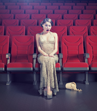Surprised beautiful girl in an empty cinema. Creative concept photo