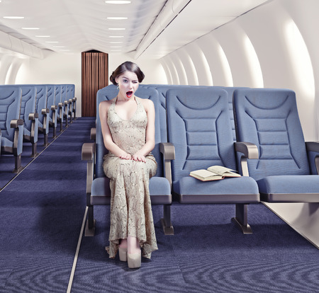 first plane: Surprised girl in an airplane. Creative concept