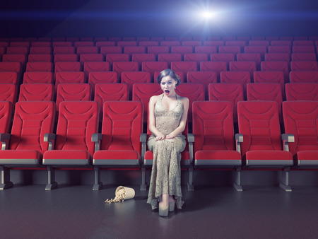 sits on a chair: Surprised beautiful girl in an empty cinema. Creative concept