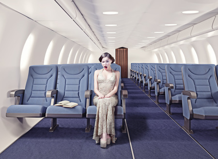 Surprised girl in an airplane. Creative concept photo