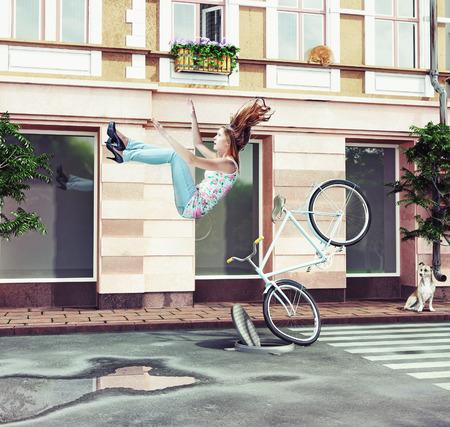 소녀 도시 거리에 그녀의 자전거에서 떨어지는. 창의적인 개념