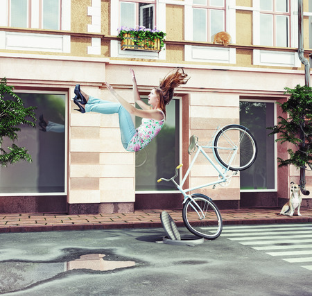 girl falling off her bicycle on city street. creative concept