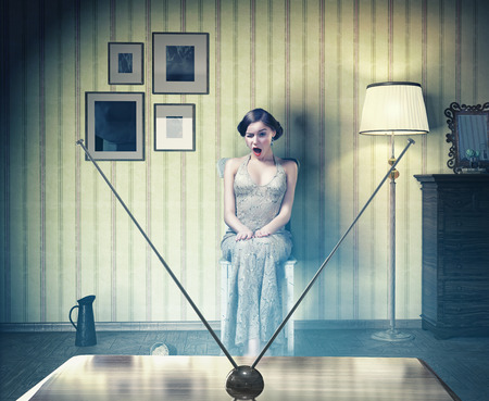horror movies: Surprised beautiful girl in the vintage interior,watching tv. Creative concept