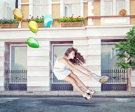 Ballons volent avec une belle jeune fille. Concept créatif