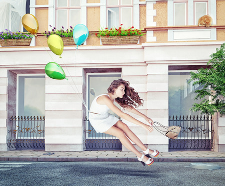conceptual cute: Balloons fly with young beautiful girl. Creative concept