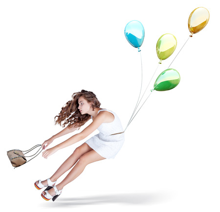 conceptual cute: Balloons fly with young beautiful girl. Isolated Creative concept