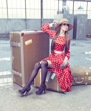 girl sitting on a suitcase waiting for travel photo