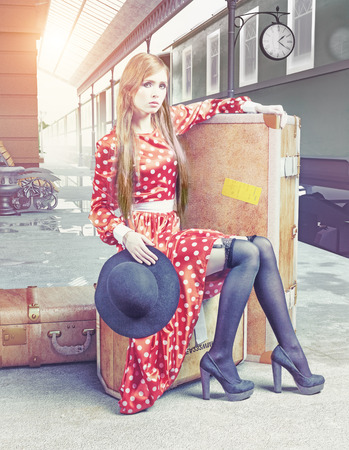 The girl sitting on the suitcase waiting at the retro railway station photo