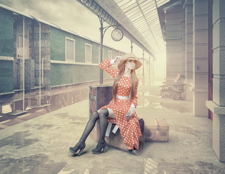 The girl sitting on the suitcase waiting at the retro railway station. Vintage color cards style photo