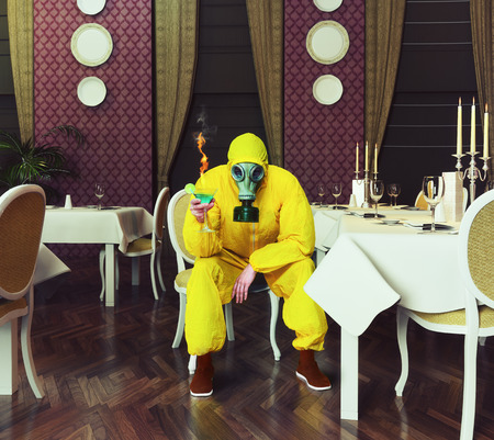 the man in a protective coverall sitting in an empty restaurant with a drink. Photo combination creative concept