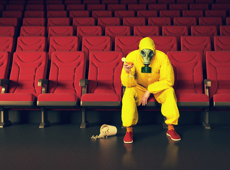 theatre masks: the man in a protective coverall  sitting in an empty theater. Creative concept